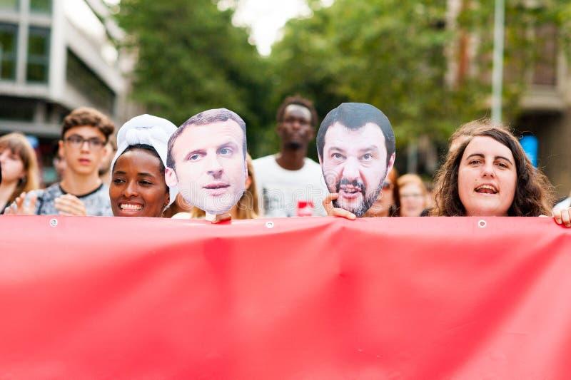Барселона, Испания 17-ое июля 2019: молодой африканец и европейские женщины маршируют держащ знамя в протесте против иммиграционн стоковые фото