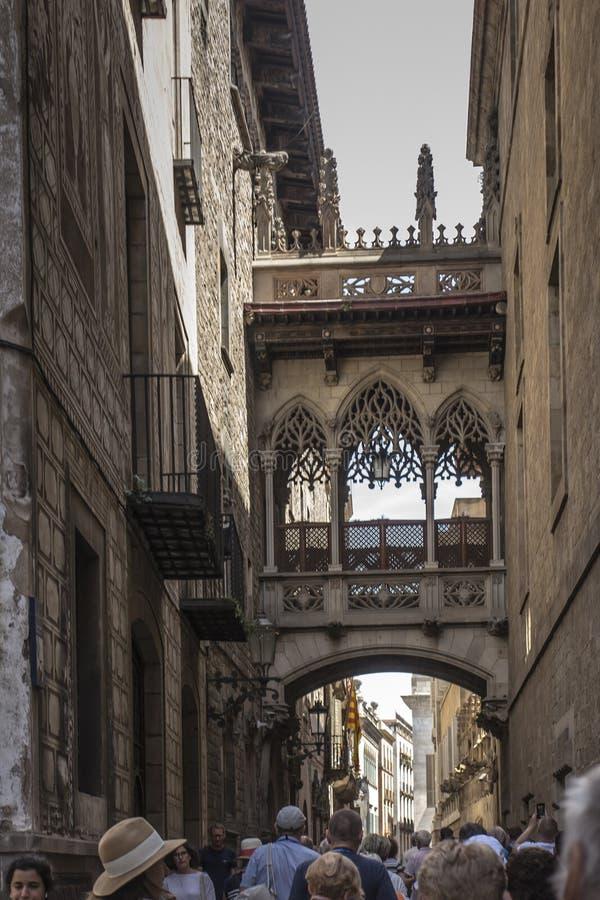 БАРСЕЛОНА, ИСПАНИЯ - 22-ое июня 2019: Pont del Bisbe и узкая улочка в готическом квартале в Барселоне стоковое изображение rf
