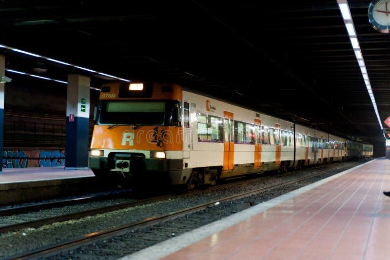 Барселона, Испания - 3-ье января 2019: региональный испанский поезд приезжая в небольшой железнодорожный вокзал города с подполье стоковые фото