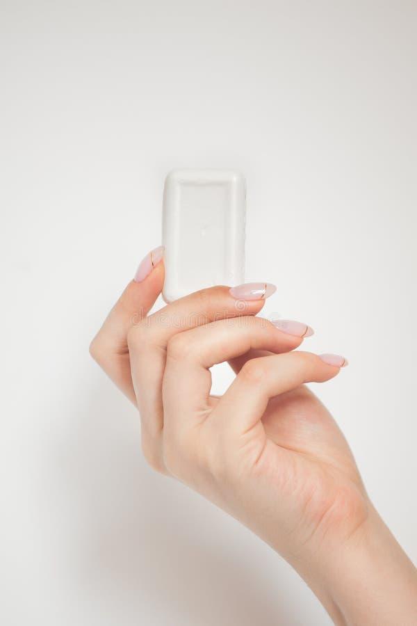 Бар мыла в женской руке стоковые изображения