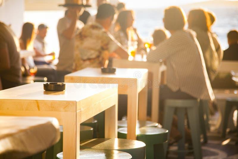 бар пляжем - фокус захода солнца на таблице стоковое изображение