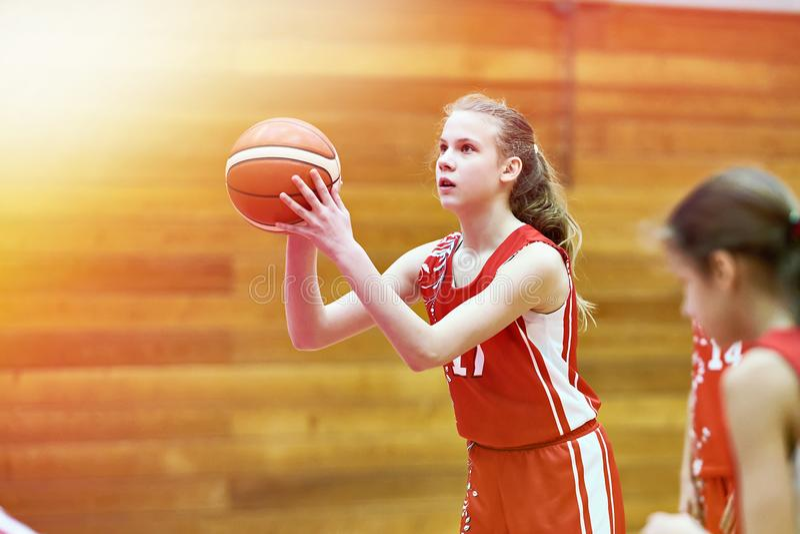 Баскетболист девушки бросает шарик в игре стоковое фото rf