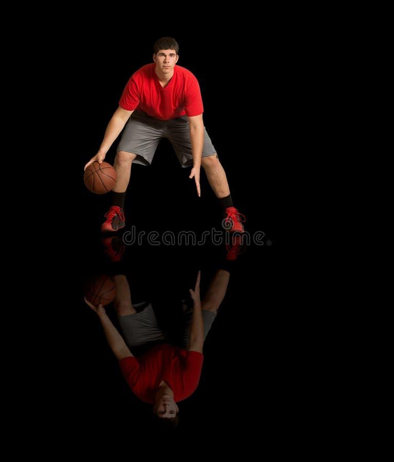 Баскетболист и его отражение на черном поле стоковое изображение