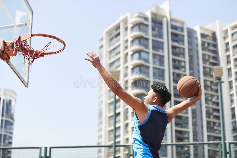 Баскетбол молодого азиатского взрослого человека dunking стоковые фотографии rf