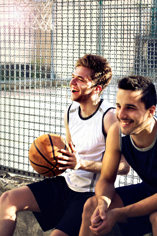 Баскетболисты принимают пролом сидя на низкой стене стоковые изображения