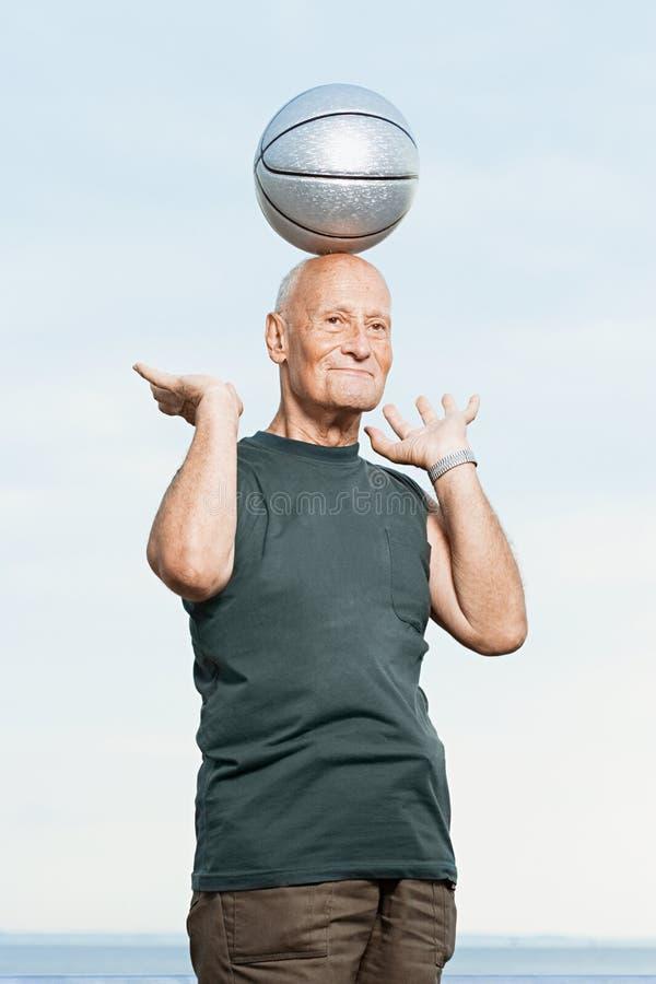 Баскетбол человека балансируя на его голове стоковая фотография rf