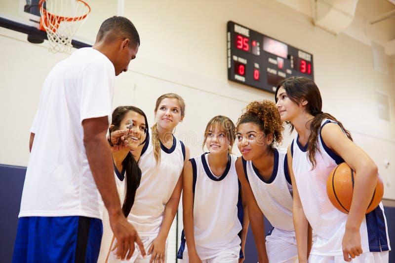 Баскетбольная команда средней школы имея разговаривать команды с тренером стоковая фотография