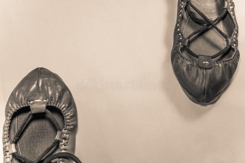 Баскская женщина танцев 2 и ботинки человека кожаные на русом взгляд сверху предпосылки против стоковое фото