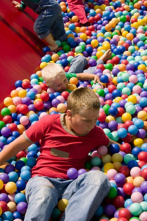 бассеин мальчиков шарика цветастый играя стоковая фотография