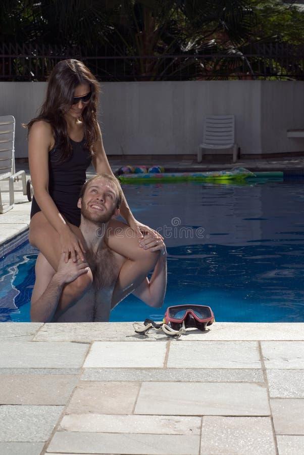 бассеин s человека взваливает на плечи вертикальную женщину стоковые фотографии rf