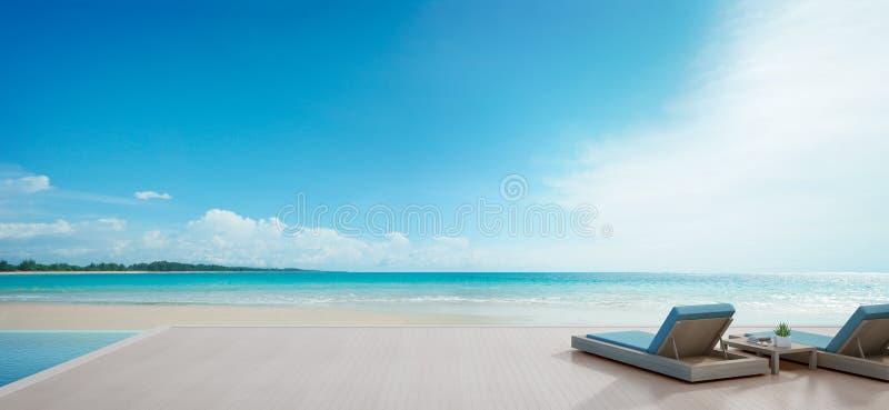 Бассейн вида на море около террасы и кровати в современном роскошном пляжном домике с предпосылкой голубого неба, кресла для отды стоковое фото