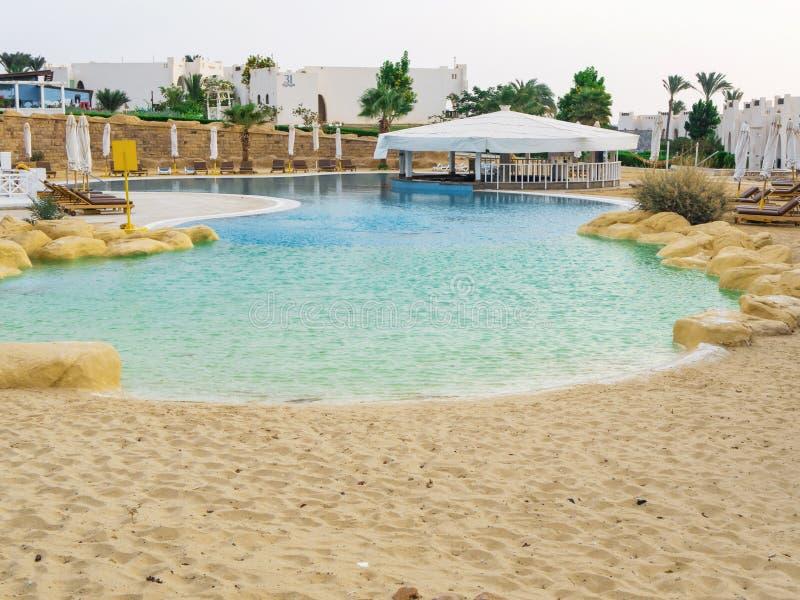 Бассейн с входом песка в Египет Пустые шезлонги около бассейна на рассвете стоковое фото rf