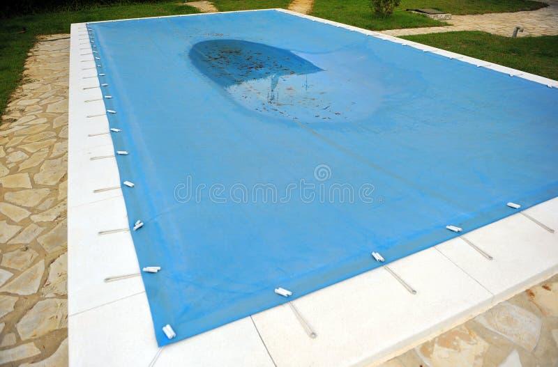 Бассейн с голубым брезентом для защиты в зиме стоковое изображение