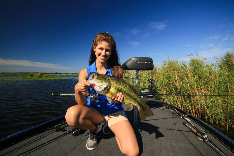 Бас рта удерживания женщины большой уловил рыбную ловлю от шлюпки стоковое изображение