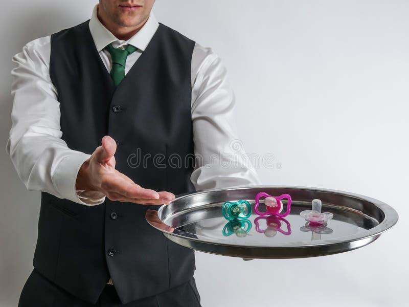 Батлер/кельнер держат серебряный поднос с pacifiers для избалованных детей стоковые фото