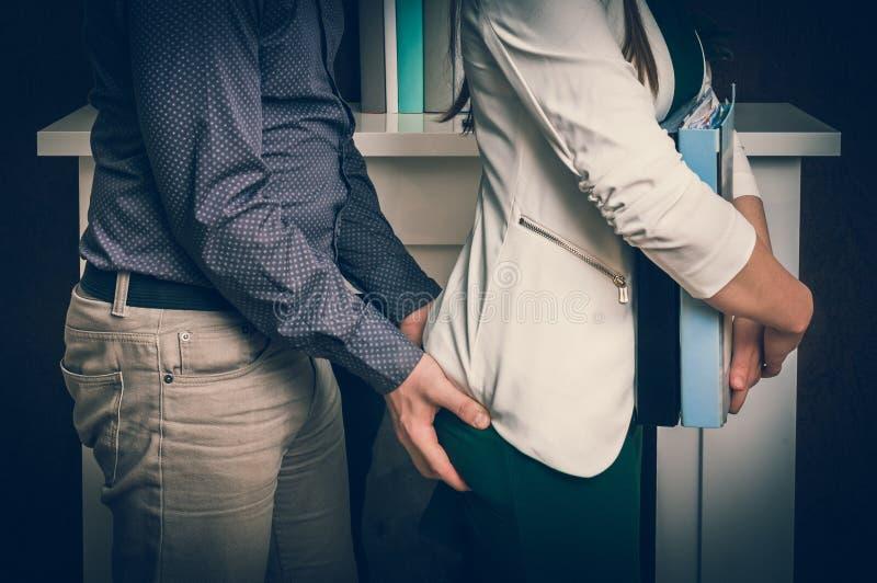 Батт ` s женщины человека касающий - сексуальные домогательства в офисе стоковое изображение