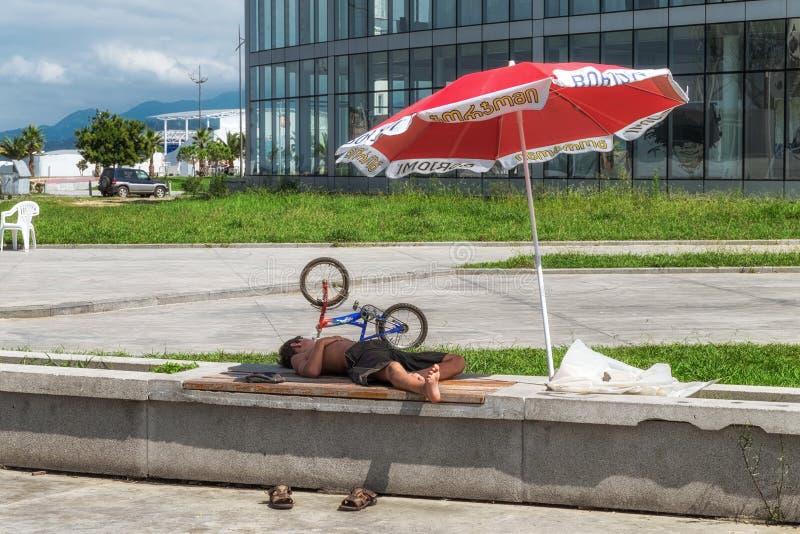 Батуми Georgia - 2-ое сентября 2014 Sleepeng мальчика на стенде улицы под ubrella стоковая фотография
