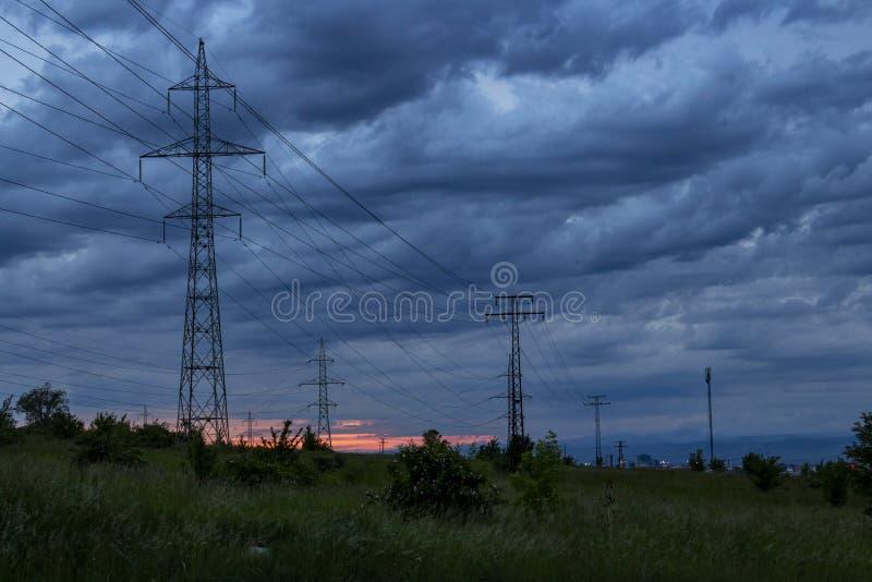 Башни передачи против драматического неба захода солнца overcast стоковые изображения rf