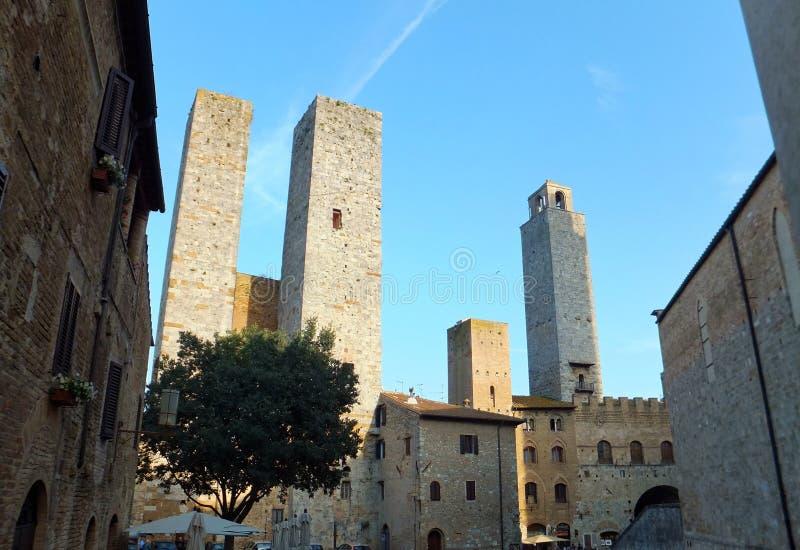 Башни San Gimignano в Тоскане, Италии против темносинего неба, окружая квадрат выровнянный со старыми историческими зданиями стоковая фотография