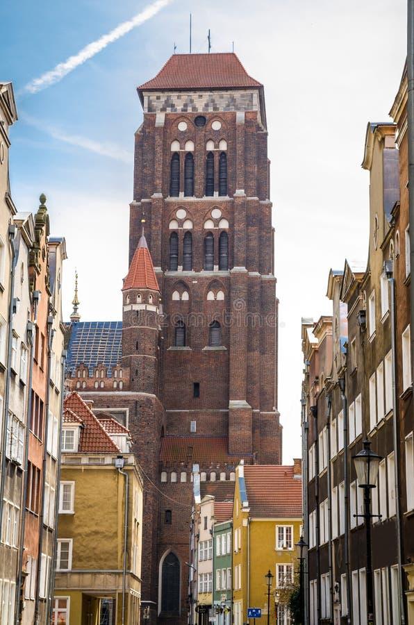 Башня кирпича взгляда собора церков St Marys девой марии базилики благословленного предположением от узкой улочки с типичное крас стоковые фотографии rf