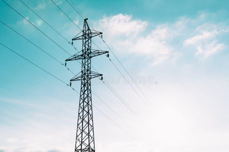 Башня линии электропередач электричества на голубой предпосылке облаков стоковое фото