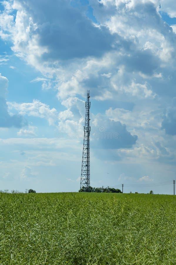 Башня мобильной телефонной связи против голубого неба с белыми облаками стоковая фотография