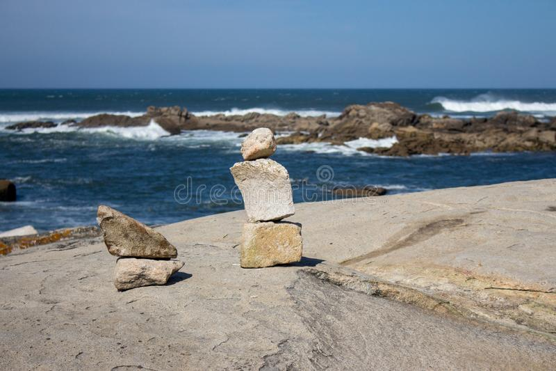 Башня небольших камней на побережье океана с утесами на предпосылке Seascape с каменным искусством Концепция баланса и сработанно стоковое фото rf