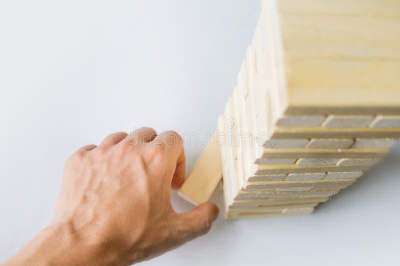 Башня от деревянных блоков и руки ` s человека принимает один блок стоковые фотографии rf