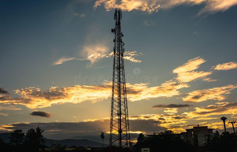 Башня радиосвязи клетчатая в небе захода солнца стоковые изображения