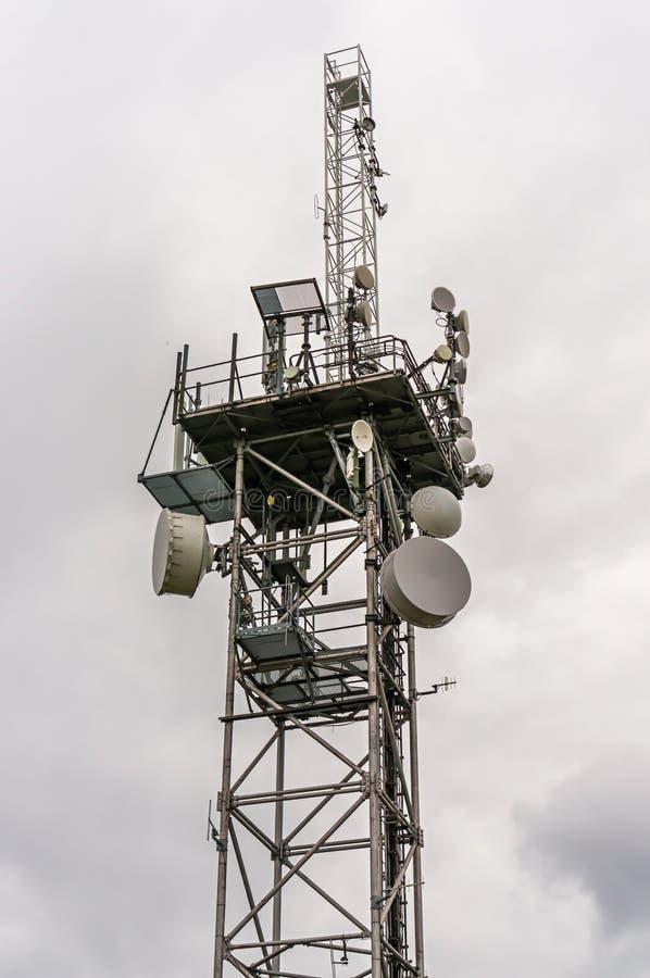 Башня радиосвязи с антеннами передатчиков и параболами стоковое фото