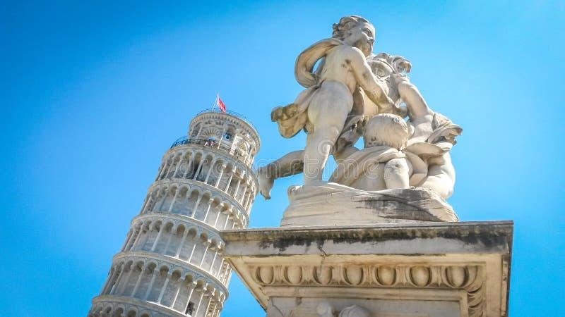 Башня склонности Пизы и статуя херувимов подогнали ангелов поддерживая пятку башни, Пизы, Тосканы, Италии стоковое фото