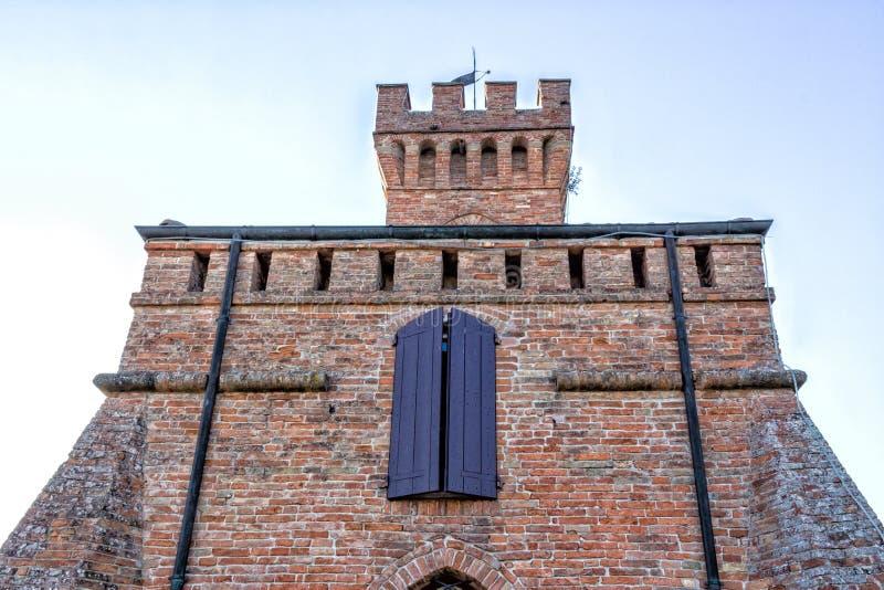 Башня с часами кирпичной стены Crenellated с фиолетовым окном стоковое фото