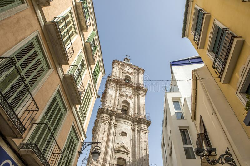 Башня церков поднимая вверх между классическими зданиями в центре города Малаги, Испании стоковая фотография