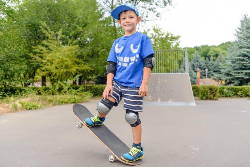 Балансировать счастливого мальчика практикуя на скейтборде стоковые изображения