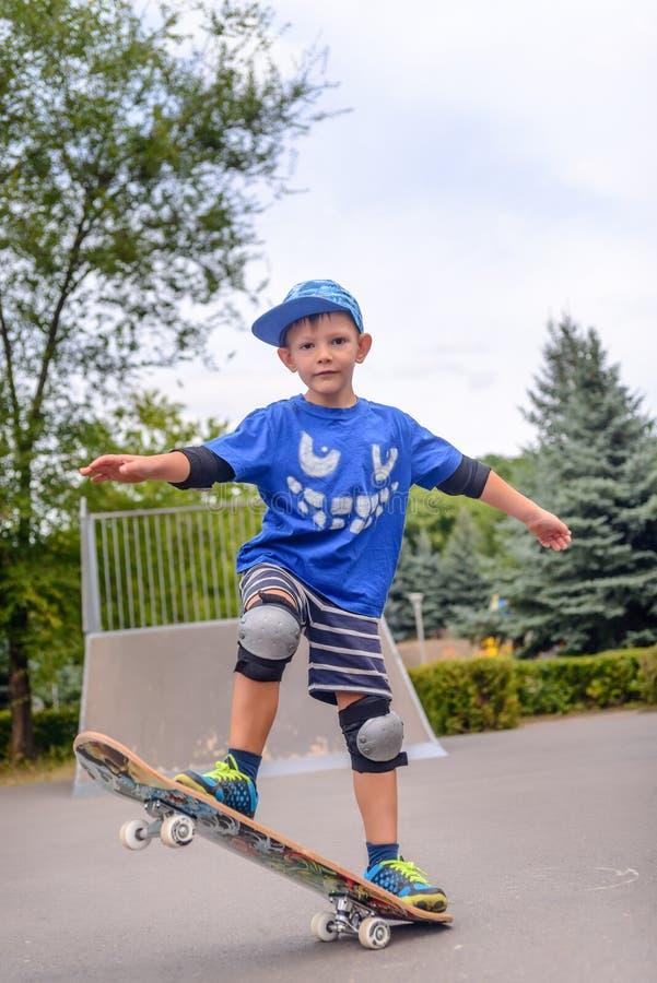 Балансировать счастливого мальчика практикуя на скейтборде стоковые изображения rf