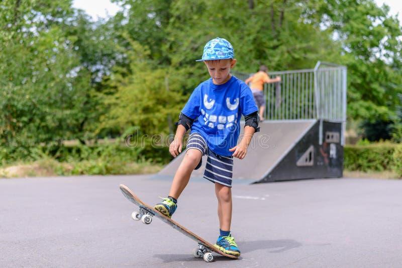 Балансировать счастливого мальчика практикуя на скейтборде стоковая фотография