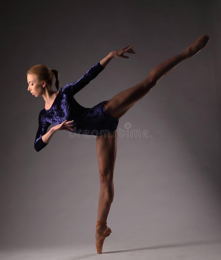 Балерина в голубом обмундировании представляя на пальцах ноги, съемке студии На одной ноге стоковое изображение rf