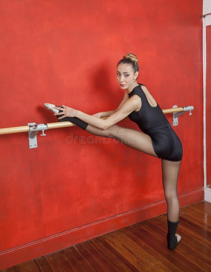 Балерина практикуя на баре балета в студии стоковая фотография