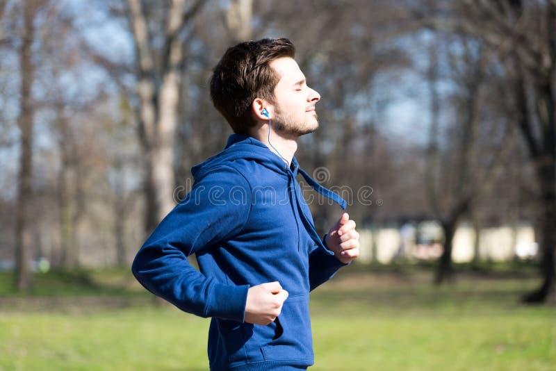 Бега молодого человека через парк стоковая фотография