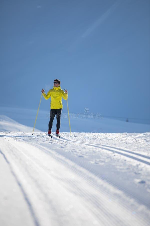 Беговые лыжи молодого человека на зимний день стоковые фотографии rf