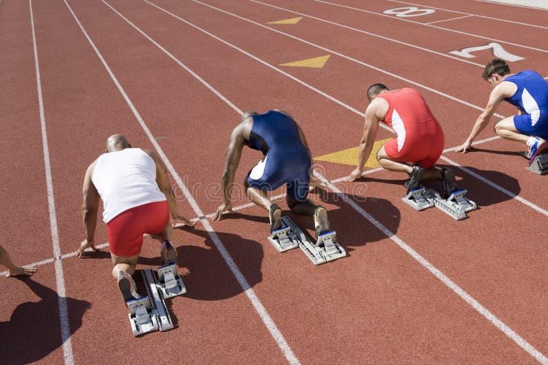 Бегуны на исходном рубеже готовом для того чтобы участвовать в гонке стоковое изображение