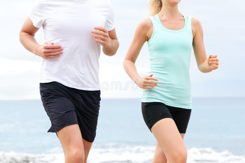 Бегуны - люди бежать на midsection пляжа стоковые фото