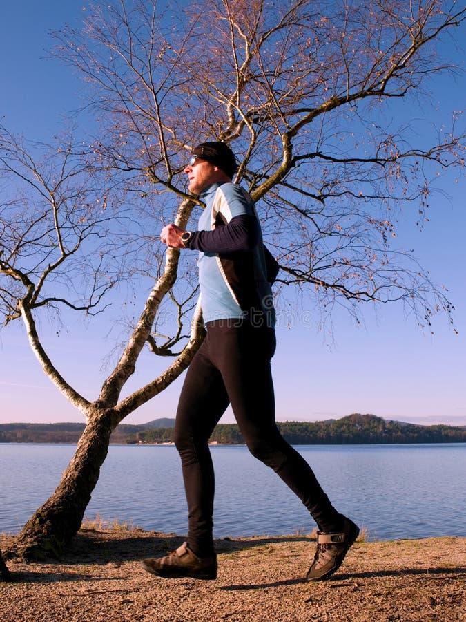 Бегун в голубой рубашке и черные leggins вдоль дерева на береговой линии Спорт и здоровая принципиальная схема уклада жизни стоковое фото rf
