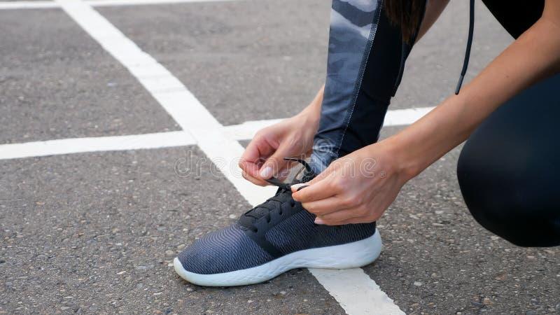 Бегун девушки связывая шнурки для jogging ее ботинки на дороге в парке стоковые фото