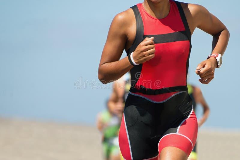 Бегун женщины бежать на гонке триатлона стоковые изображения rf