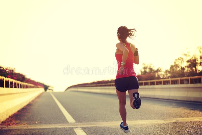 бегун женщины бежать на дороге города стоковые изображения
