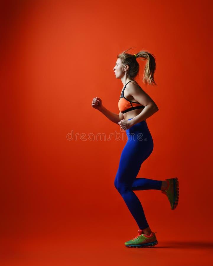 Бегун женщины в силуэте на красной предпосылке динамическое движение Взгляд со стороны стоковое фото