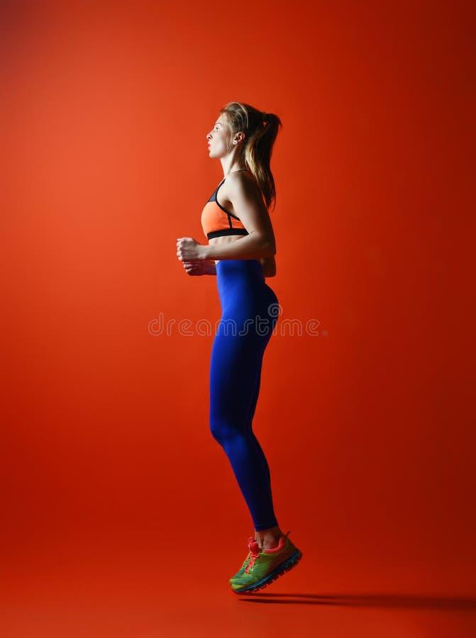 Бегун женщины в силуэте на красной предпосылке динамическое движение Взгляд со стороны стоковые изображения rf