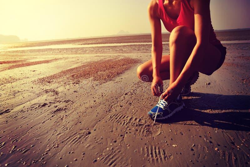 Бегун женщины связывая шнурок перед бежать на пляже стоковые фото