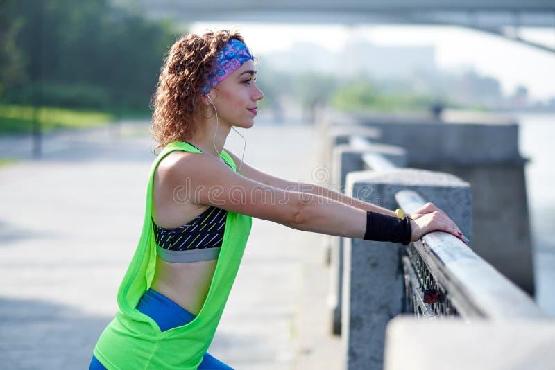 Бегун женщины фитнеса здоровый ослабляя после бега outdoors наслаждаясь взгляда на портовом районе стоковые фото